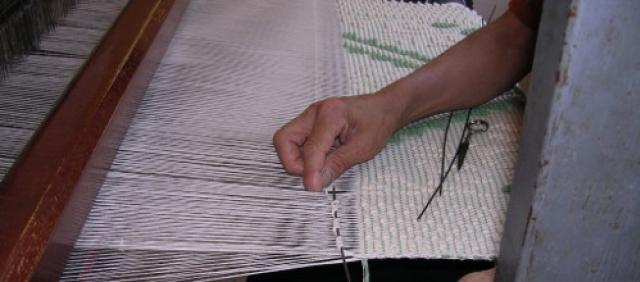 Tessitrice a lavoro su tappeto sardo a pibiones